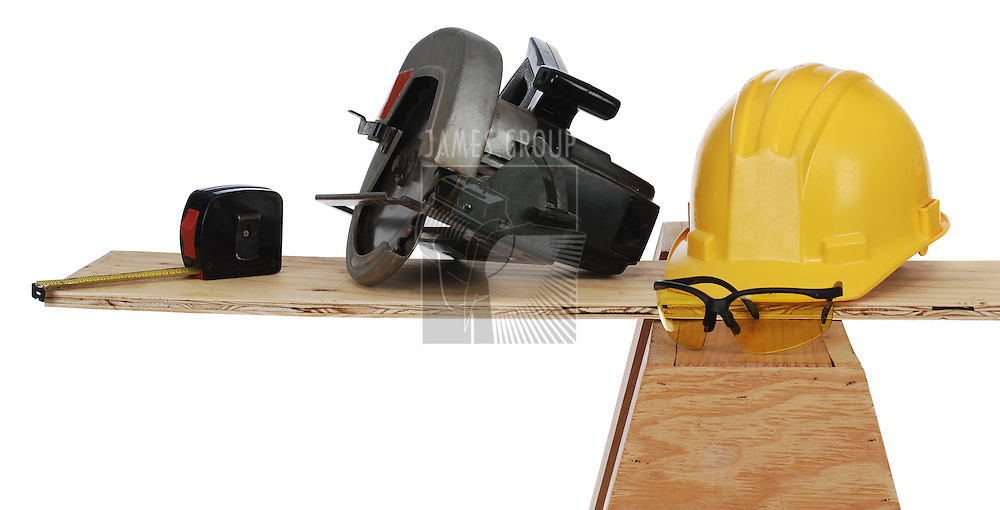 tape measure, power saw, hard hat and wooden plank resting on a saw horse