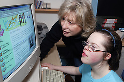 Teenage Downs Syndrome girl with woman looking at a computer screen,