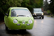 A green electric car known as the Xebra, manufactured by the Zap corporation on the road in Bend, Oregon.  The ZAP motor company stands for Zero Air Pollution, and manufactures and distributes it vehicles through auto dealers in the USA.
