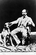 Charles Dickens (1812-1870) English author. Photograph of Dickens seated with dog at side. Taken towards end of his life.