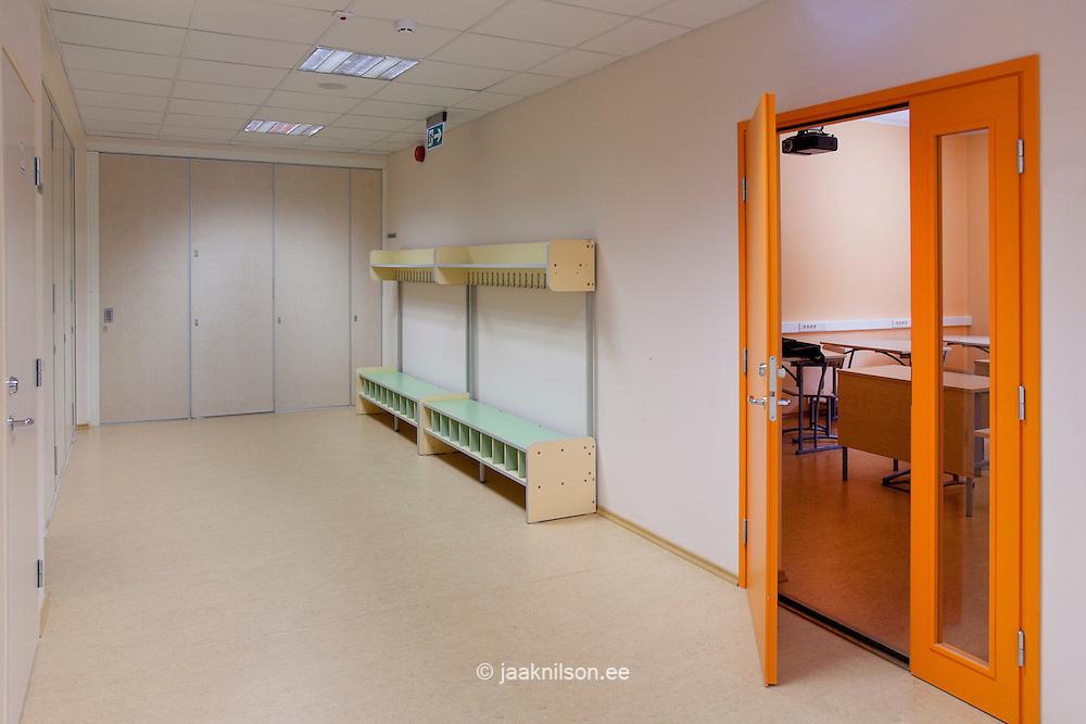 Corridor with coat rack and shoe lockers. Open colourful door into classroom in Village school in Metsapoole, Estonia.