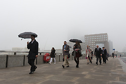 © Licensed to London News Pictures. 11/05/2016. LONDON, UK.  Early morning commuters cross London Bridge in London during foggy and wet weather this morning.  The normally visible London Shard has disappeared. Photo credit: Vickie Flores/LNP