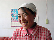 Woman in her house at Guancai Village. Ningxia Province, China.