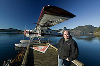 A Beaver float plane and pilot wait for passengers embarking from the remote community of Surge narrows in the Discovery Islands off of British Columbia's central coast.  Surge Narrows, Read Island, Discovery Island's, British Columbia, Canada.
