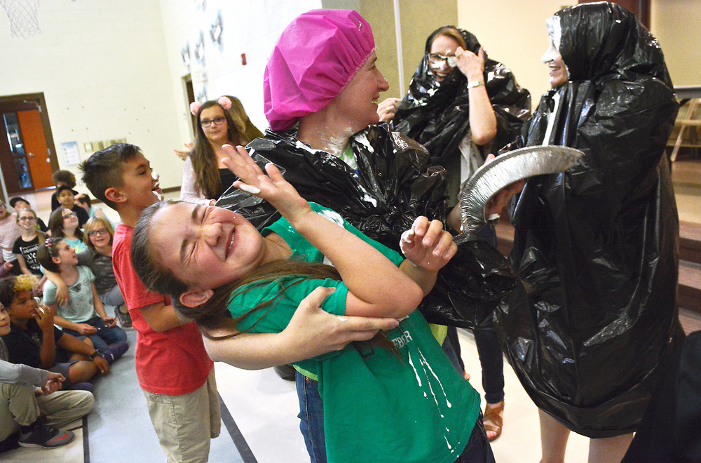 Cielo Azul teacher Kim Ayres, wearing a pink cap, plays with her student Kaylee Case after being hit with a whipped cream pie, Wednesday, May 17, 2017, at Cielo Azul Elementary in Rio Rancho, N.M. This was the first year that students who took the PARCC exams were given incentives: to smash a pie-in-face or shoot silly string at a teacher or administrator. Kids who best followed the strategies were chosen. In total, about 18 pies were smashed in teachers' faces.  (Marla Brose/Albuquerque Journal)