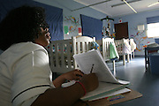 Sonja, a health worker, is compiling some forms at Thembacare HIV+ children's care hospice in Athlone, Cape Town.