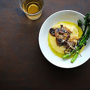 Soft polenta with mushrooms and seared broccolini on wooden surface along with drink.