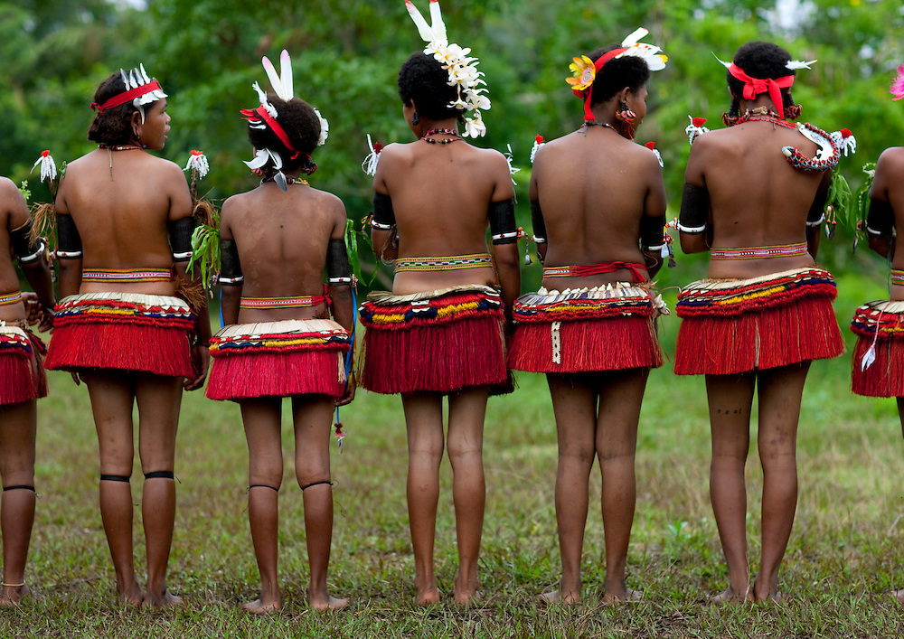 Girls take part in battles and dance topless, only wearing red grass skirts, shells, feathers, and flower pollens. Trobriand Islands (aka the Kiriwina Islands), off the eastern coast of Papua New Guinea in Milne Bay Province.
