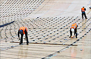 Nederland, Nijmegen, 12-3-2015 Aan de overkant van de Waal bij Lent wordt druk gewerkt aan het creeren van een nevengeul in de rivier om bij hoogwater een betere waterafvoer te hebben. De zandzuiger in het water bij de nieuwe recreatiekade. Op de voorgrond werkzaamheden aan de vernieuwde n325. Het is een omvangrijk project waarbij onder meer de pijlers van het spoorviaduct een bredere basis moeten krijgen omdat die straks in de loop van het water staan. Ook de n325 die vanaf de Waalbrug naar Arnhem loopt moet over 400 meter opnieuw worden aangelegd omdat het talud vervangen wordt door pijlers. De weg wordt via een bypass omgeleid. Het dorp veurlent komt op een kunstmatig eiland te liggen met twee bruggen als ontsluiting. Een voetgangersbrug en de andere voor normaal verkeer. Inmiddels begint de nieuwe kade aan de noordkant van deze geul vorm te krijgen. Ruimte voor de rivier, water, waal. In de nieuwe dijk wordt een drempel gebouwd die stapsgewijs water doorlaat en bij hoogwater overloopt. Measures taken by Nijmegen to give the river Waal, Rhine, more space to flow during highwater and to prevent the risk of flooding. Room for the river. Reducing the level, waterlevel. Aanvulling 18-5-2015Tientallen portugese bouwvakkers die via bemiddelingsbureau, uitzendbureau, rimec hier werkten blijken uitgebuit en onderbetaald te zijn. Zij werkten vooral aan de bouw, de bekisting en ijzervlechting, van de verlengde waalbrug. Het programma Zembla heeft dit vastgesteld.Foto: Flip Franssen/Hollandse Hoogte
