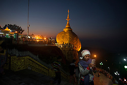 "A pilgrim takes a auto portrait with Kyaiktiyo Pagoda ""Golden Rock"" in her background at Kyaiktiyo, Myanmar on Saturday, 1, Feb. 2014."