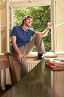 Young man sitting on sill of living room window