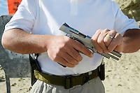Man loading hand gun at firing range, mid section