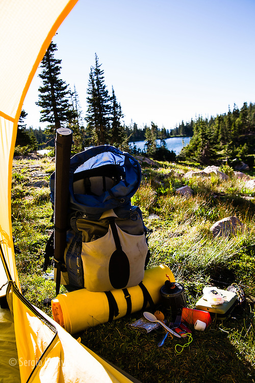 Classic rugged Colorado alpine landscape as seen from a tent during summer; wild flowers, creeks, alpine lakes and pine forests.