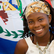 Rita May, cultural researcher from House of Culture,  in front of Belize flag at Creole Festival, Belize City, Belize
