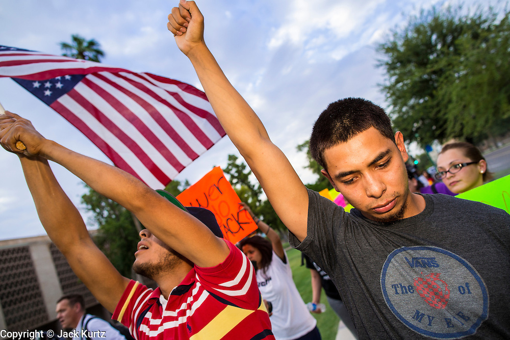 15 AUGUST 2012 - PHOENIX, AZ:   A man clenches his fist while he marches to the Arizona State Capitol. About 200 people, mostly DREAM Act  (an acronym for Development, Relief, and Education for Alien Minors) students and their family members, marched on the Arizona State Capitol in Phoenix Wednesday after Arizona Governor Jan Brewer said the state of Arizona will not give DREAM Act students any state services, including driver's licenses or tuition breaks on state universities and schools. Brewer has been a critic of President Obama's plan to defer deportations of certain undocumented young people.   PHOTO BY JACK KURTZ