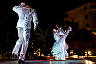 "View from behind two Mexican dancers in white costumes performing La Bamba, the traditional dance symbolic of ""tying the knot"" and celebration of marriage. The woman holds the lace skirt of her dress in the air as she turns on the red ribbon on stage."