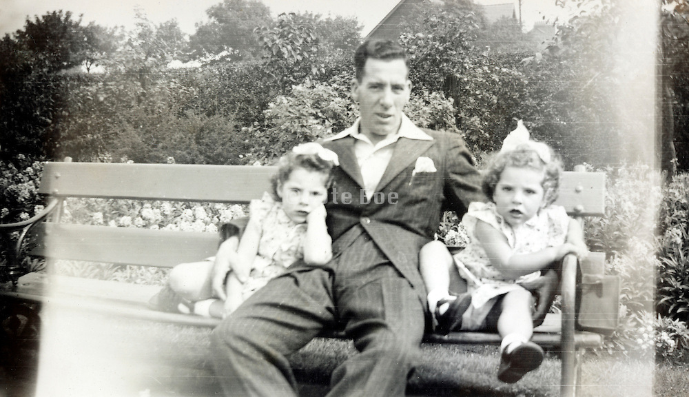 father with twins on a outdoor bench 1950