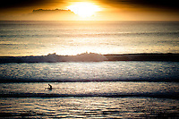 A surfer comes in from a surf session just before sunset at Uluwatu, Bali, Indonesia.