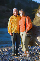 Senior couple standing on rocky shore