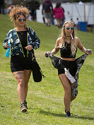© Licensed to London News Pictures .06/06/2015. Manchester , UK.  Two women arrive in the sunshine at The Parklife 2015 music festival in Heaton Park , Manchester . Photo credit : Joel Goodman/LNP