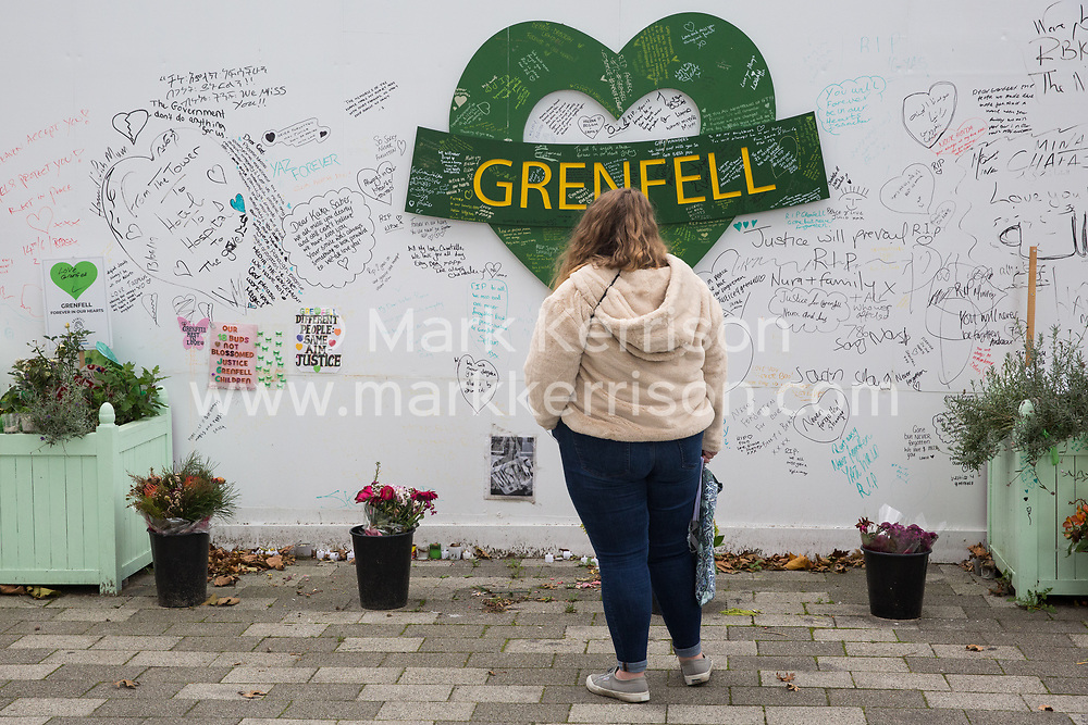 London, UK. 29 October, 2019. A woman contemplates memorials close to the Grenfell Tower. A much-delayed public inquiry report into the Grenfell Tower disaster which killed 72 people to be published tomorrow has been criticised today for its emphasis on criticism of London Fire Brigade.