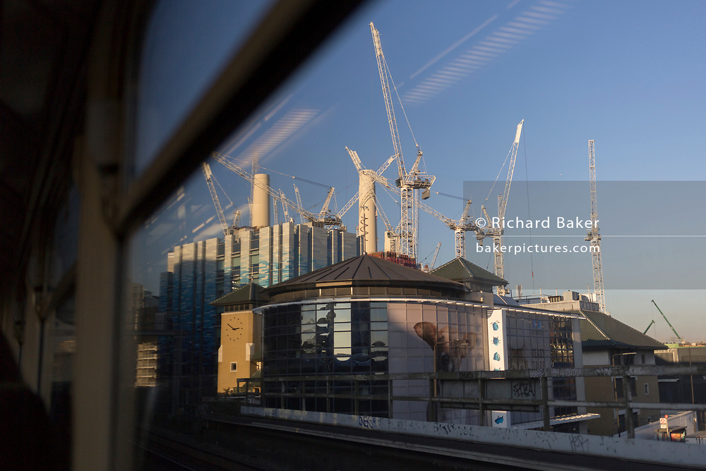 Seen from the window seat of a train carriage that is travelling towards Victoria station, is a landscape of Battersea Dogs Home and cranes and gantries at the large Battersea Power Station construction site, in London, England, on 4th December 2019.