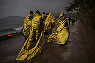 Refugees and migrants are cover themselves with thermal blankets after their arrival on a dinghy from the Turkish coast to the village of Skala Sykaminias on the northeastern Greek island of Lesbos on Friday, Oct. 23, 2015. The International Office for Migration says over the last week, Greece experienced the largest single weekly influx of migrants and refugees in 2015, at an average of some 9,600 per day. (AP Photo/Santi Palacios)
