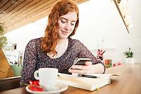 Creative Workplace, junge Frau, kreativ, Kaffeepause, Arbeiten außerhalb des Büros, Mobiltelefon, Restaurant, Österreich, Horn