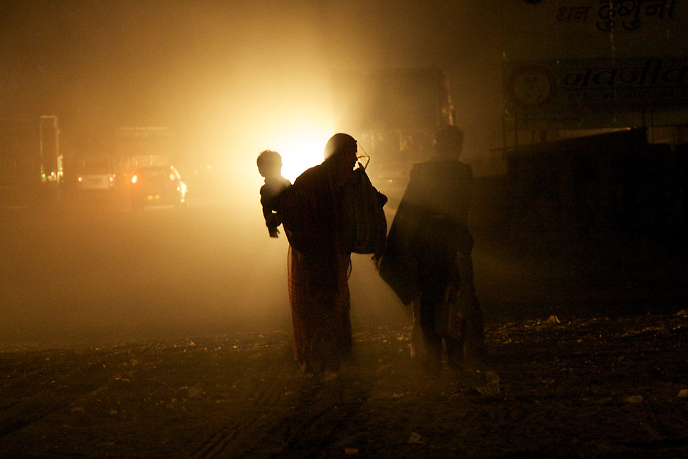 India. A Mother with her child is walking at night in the street of Pushkar.  Photo by Lorenz Berna