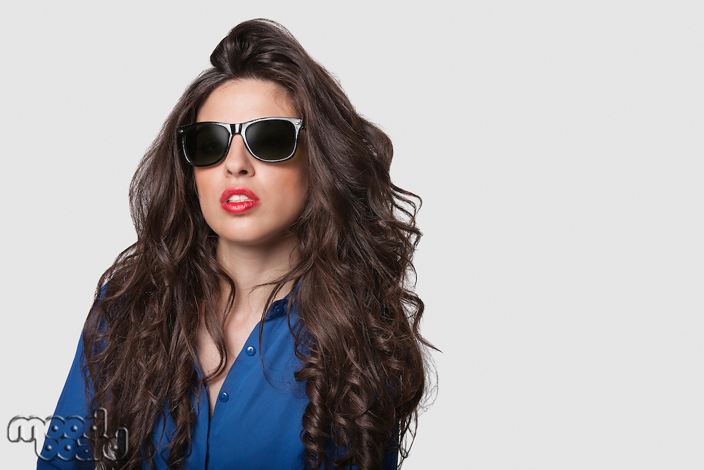 Portrait of an attractive young woman wearing sunglasses against gray background