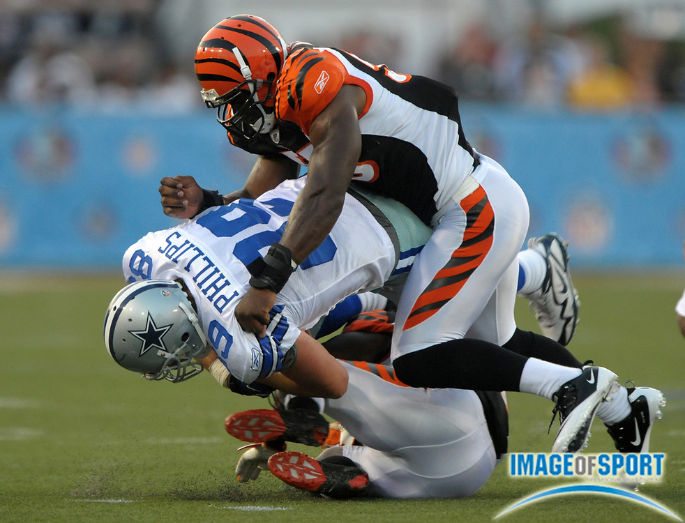 Aug 8, 2010; Canton, OH, USA; Dallas Cowboys tight end John Phillips (89) is tackled by Cincinnati Bengals linebacker Keith Rivers (55), top, and corneback Adam Jones (24) after an eight-yard gain during the first quarter of a preseason game at Fawcett Stadium. Photo by Image of Sport
