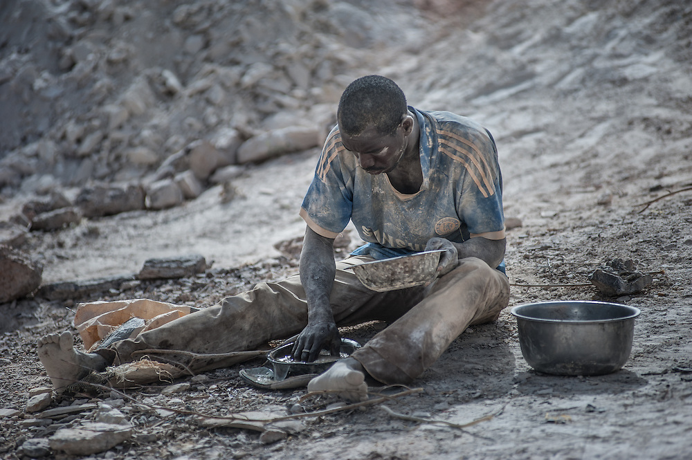 Nobsin, Burkina Faso - 13 May 2014: a man covered in dry mud sits on the ground searching for gold. It is estimated that around 500,000 to 700,000 teenagers and young boys, work in around 700 to 800 artisanal gold-washing sites in Burkina Faso.