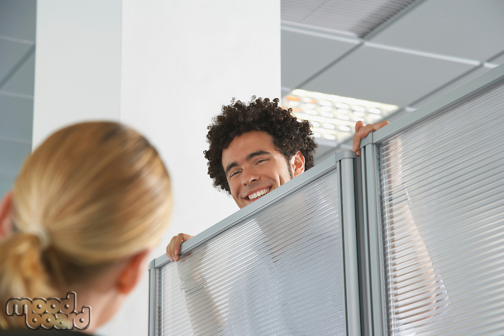 Office worker peering over cubicle wall to greet coworker in office