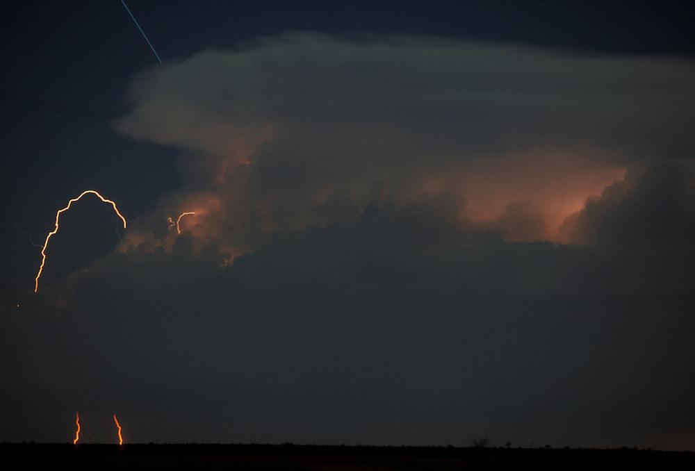 Botswana, Nxai Pan National Park, Lightning strikes from storm cloud at night, lit by moonlight above Kalahari Desert