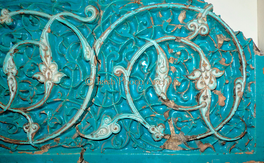 Carved Tile.  The potter made the pattern by carving into the earthenware tile.  The tile was then coated with glaze and fired.