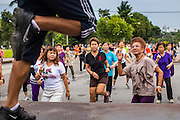 06 OCTOBER 2012 - BANGKOK, THAILAND: Class participants follow their instructor during a public exercise class in Lumphini Park in Bangkok. The Thai government promotes exercise classes as a way staying healthy. Lumphini Park is 142 acre (57.6-hectare) park in Bangkok, Thailand. This park offers rare open public space, trees and playgrounds in the congested Thai capital. It contains an artificial lake where visitors can rent boats. Exercise classes and exercise clubs meet in the park for early morning workouts and paths around the park totalling approximately 1.55 miles (2.5 km) in length are a popular area for joggers. Cycling is only permitted during the day between the times of 5am to 3pm. Smoking is banned throughout smoking ban the park. The park was created in the 1920's and named after Lumbini, the birthplace of the Buddha in Nepal.   PHOTO BY JACK KURTZ