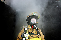 "JEROME A. POLLOS/Press..Coeur d'Alene firefighters Justin Wearne exits out of a ""burn room"" Monday during a training routine in the Spokane Valley for five new firefighters hired by the city."