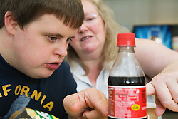 Teenage boy with Downs Syndrome looking at label on a bottle of cola,
