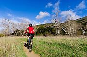 Female mountain biker in Sycamore Canyon, Point Mugu State Park, California USA