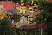 Torn and weathered remnants of a communist party banner by a roadside in China.