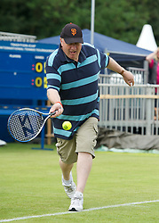 LIVERPOOL, ENGLAND - Wednesday, June 20, 2012: A teacher tries his hand at tennis during a kids' day at the Medicash Liverpool International Tennis Tournament at Calderstones Park. (Pic by David Rawcliffe/Propaganda)