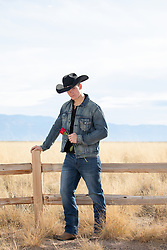 young good looking cowboy holding a red rose on a ranch