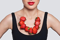 Mid section of a woman wearing strawberry necklace over gray background
