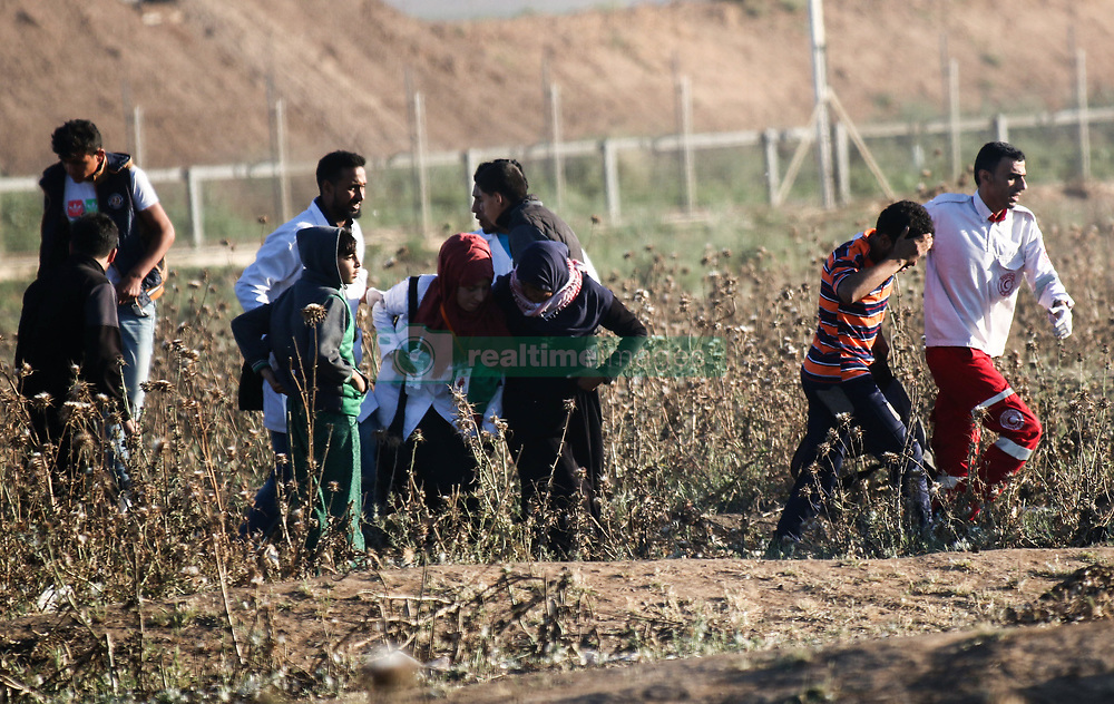 May 3, 2019 - Gaza, Palestine, 3 May 2019. Clashes occur between Palestinian protesters and the Israeli forces near Abu Safiya, in the northern Gaza strip, in this week Great March of Return rally, while paramedics rush to rescue and treat the injured protesters. The weekly Gaza border protests were attended by around 5,000 Palestinians, and according to Gaza Health Ministry Palestinian protester Raed Abu Teir, 19, was shot dead by live Israeli fire while 40 demonstrators were wounded as Israeli soldiers fired tear gas, rubber bullets and live gunshots at them. Some Palestinians threw stones towards the fence and the Israeli troops, and according to the Israeli army some incendiary devices were launched on Friday from Gaza into Israel, and two Israeli soldiers were wounded by Palestinian gunfire. In response to the alleged Palestinian shooting, an Israeli aircraft attacked a Hamas post in the southern Gaza strip killing two Palestinians. Border clashes have been taking place at least once a week for over a year, and since the protests began at the end of March 2018, at least 265 Palestinians have been killed and thousands have been injured, while Palestinians paramedics have been putting their lives at risk to save the injured protesters (Credit Image: © Ahmad Hasaballah/IMAGESLIVE via ZUMA Wire)