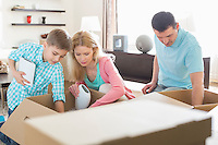 Family unpacking cardboard boxes in new house