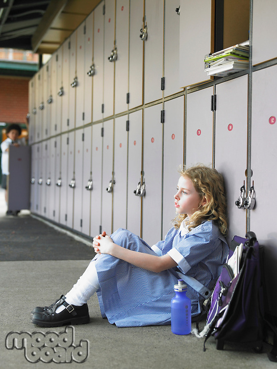 Elementary schoolgirl sitting on floor against school lockers
