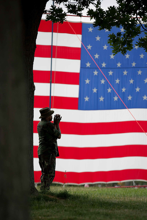 A soldier stands in the shadows of a large American flag that has been hung on the National Mall in honor of Memorial Day.