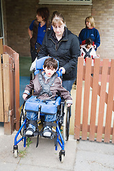 Physically disabled child being pushed in wheelchair by carer,