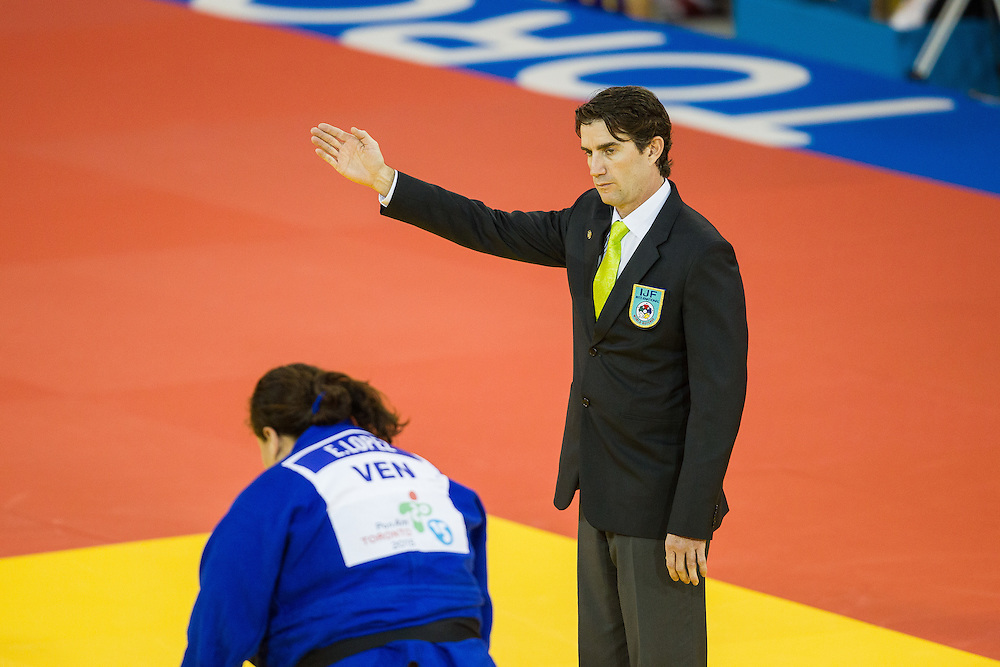 Referee Andres  Cabeiro of Guatemala signals the victory for  Maria Suelen Altheman of Brazil over Emileidys Lopez (in Blue) of Venezuela in their 1/4 final contest in the women's judo +78kg class at the 2015 Pan American Games in Toronto, Canada, July 14,  2015.  AFP PHOTO/GEOFF ROBINS