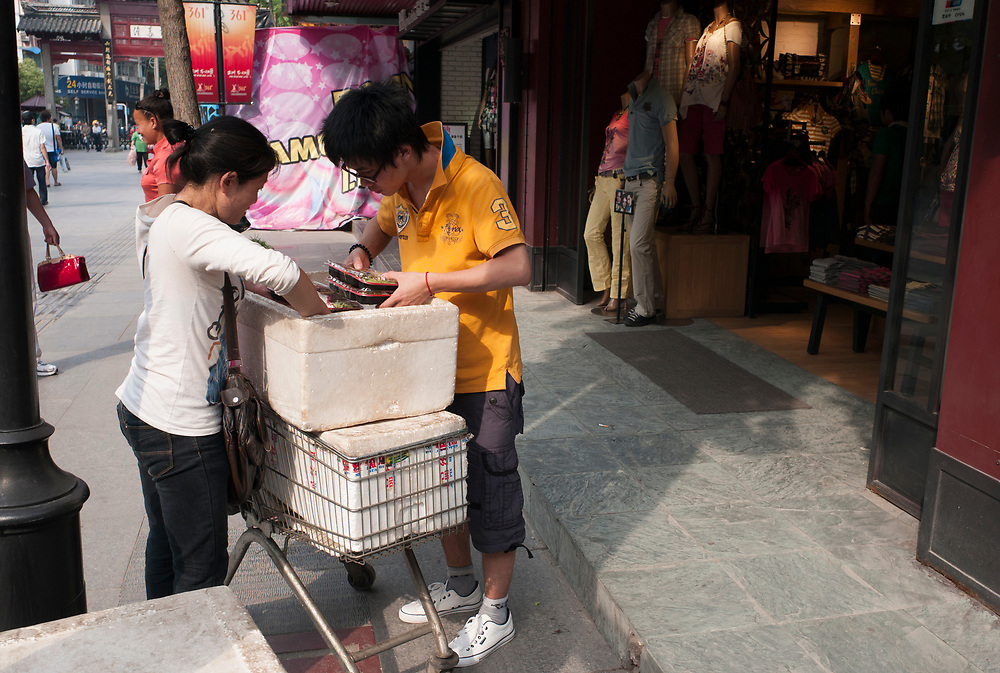 Nankin, Chine. Centre ville. Des marchants ambulants livrent des plateaux repas aux employ&eacute;s des magasins.<br /> <br /> Nanjing, China. City center. Shop employees get their lunch boxes delivered.